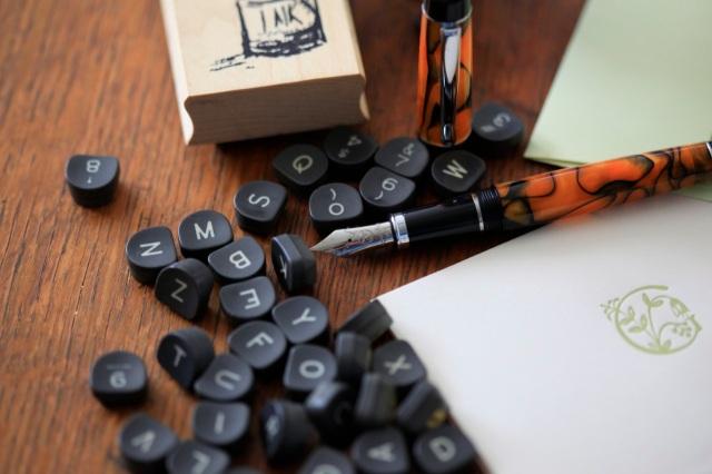 paper, pen and old typewriter keys